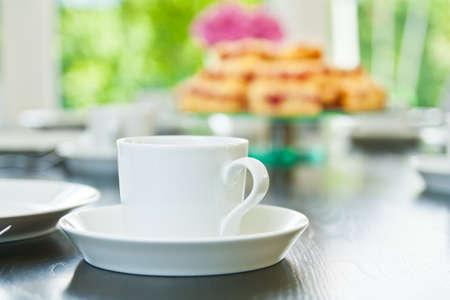 Raspberry Streusel-Kuchen auf einem Tisch mit Geschirr und Kaffeetassen in Scheiben geschnitten