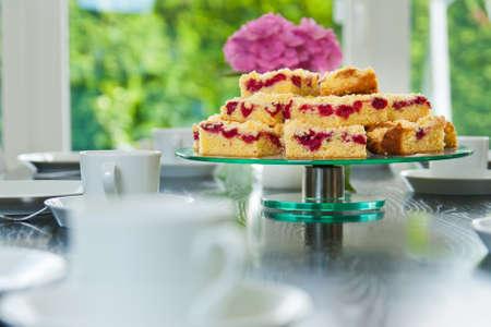 Raspberry Streuselschnecke auf einem Tisch mit Geschirr und Tassen in Scheiben geschnitten