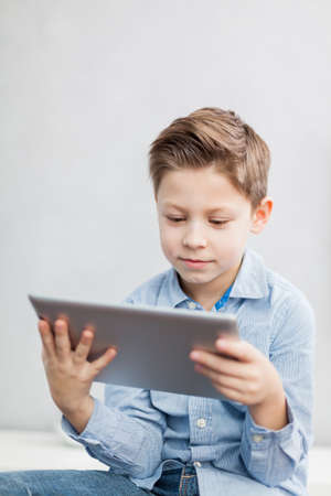 Boy sitting  in the living room using a tablet pc Stock Photo