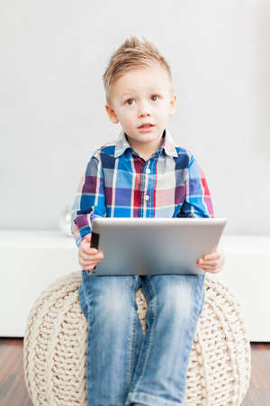 Boy sitting  in the living room using a tablet pc Standard-Bild
