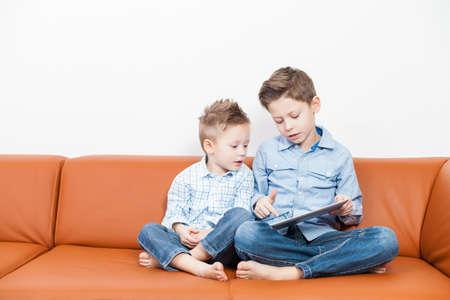 Zwei Jungen sitzen im Wohnzimmer mit einem Tablet PC Lizenzfreie Bilder