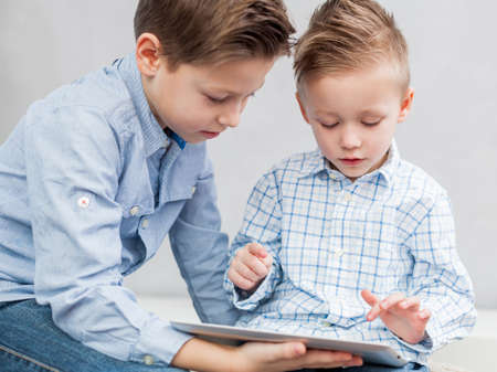 Two boys sitting  in the living room using a tablet pc photo