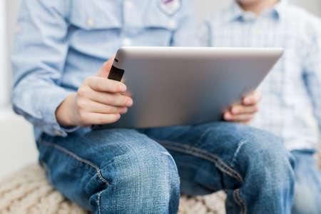 Zwei Jungen sitzen im Wohnzimmer mit einem Tablet-PC
