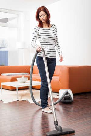 Attraktive Frau mit Staubsauger im Wohnzimmer