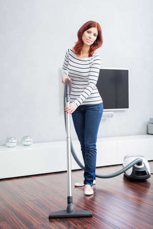 home keeping: Attractive Female with Vacuum in Living Room