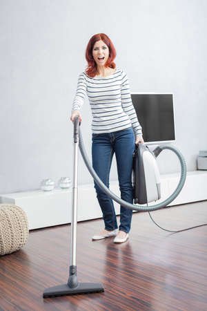 keeping room: Attractive Female with Vacuum in Living Room screaming