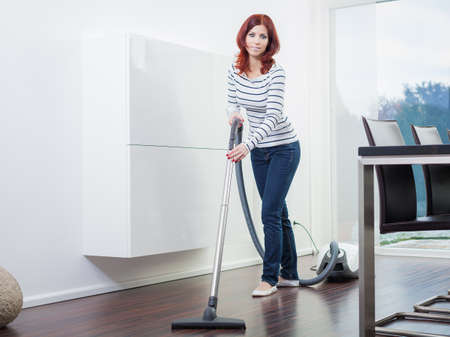 Attractive Female with Vacuum in Living Room photo