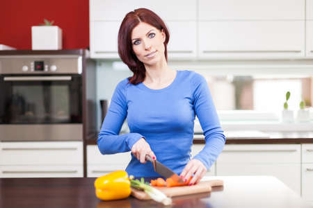 Attractive young female preparing vegetables in the kitchen Stock Photo