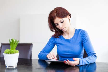 Attraktive Frau mit Tablet PC sitzen am Tisch