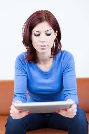 Attraktive Frau sitzt auf einer Couch mit dem Tablet PC