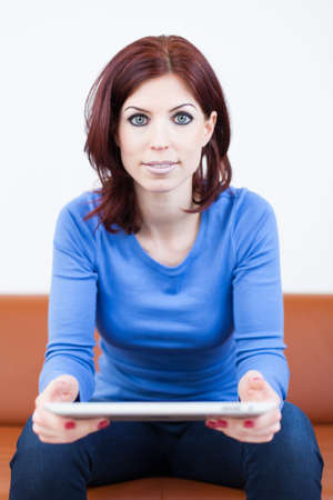 Attractive Woman sitting on a couch with Tablet PC Stock Photo - 19376360