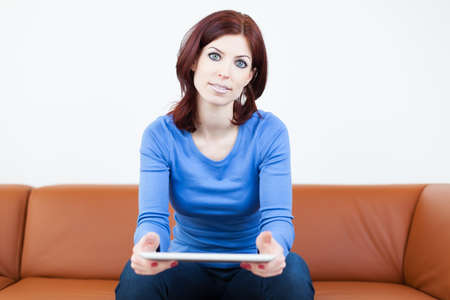 Attractive Woman sitting on a couch with Tablet PC Standard-Bild