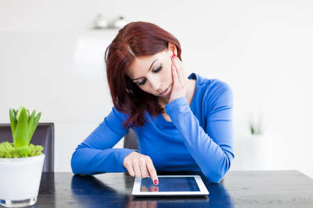 Attractive woman with Tablet PC sitting at table Stock Photo - 19376373