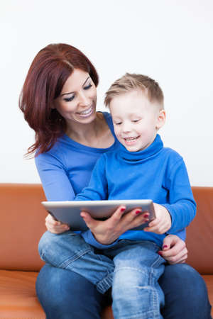 A Mother and her Son sitting on a couch using a Tablet PC Stock Photo