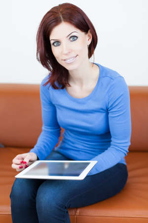 Attractive Woman sitting on a couch with Tablet PC photo