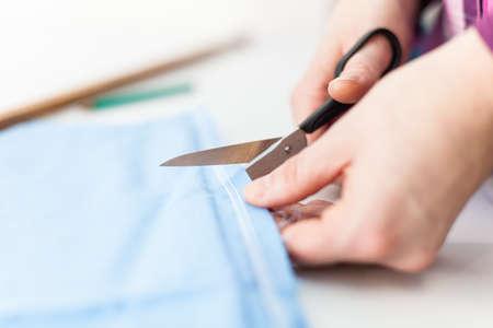 Scissors cutting blue tissue