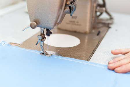 stitching machine: Sewing machine stitching blue tissue