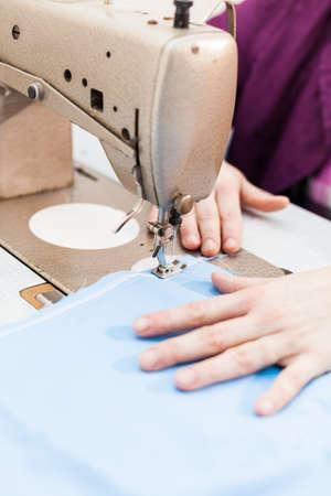 Sewing machine stitching blue tissue