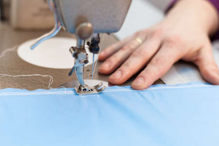 Sewing machine stitching blue tissue
