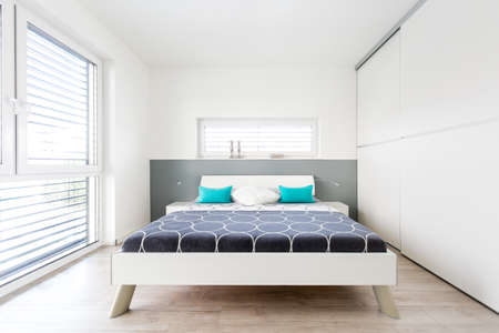 master bedroom: Modern Master Bedroom with large window and wooden floor Stock Photo