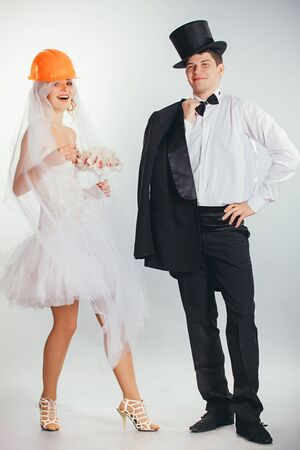 tophat: young couple of bride in helmet with veil and groom in tophat and stylish wedding clothes Stock Photo