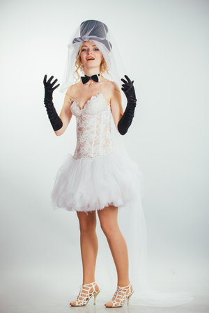 long gloves: young beautiful blonde bride in tophat with veil and stylish wedding dress with long black gloves
