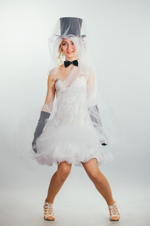 tophat: young beautiful blonde bride in tophat with veil and stylish wedding dress with long black gloves