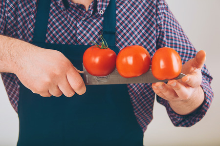 coking: man holding a tomato on the knife