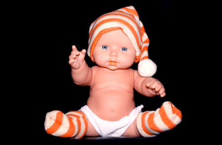 Silicone and vinyl doll with acrylic eyes. It has orange and white stripe hat and shocks. The background is black.