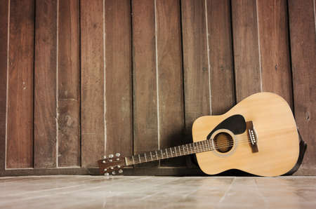 taylor: Wooden guitar lying against the wall Stock Photo