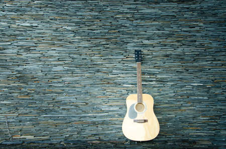 taylor: Wood guitar against wall ,background and texture Stock Photo