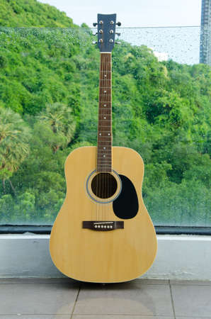 taylor: Wood guitar against wall glass ,background and texture Stock Photo