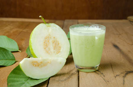 guava fruit: Guava juice and fresh Guava on wooden background Stock Photo