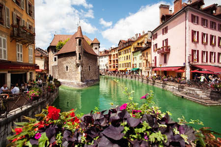 encircling: ANNECY, FRANCE - MAY 13, 2012: People walk around the River Thiou in Old Town, encircling the medieval palace perched mid-river - the Palais de lIsle