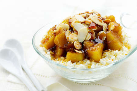 Healthy breakfast with cottage cheese, caramelized cinnamon apples, crumble and sliced almond Stock Photo