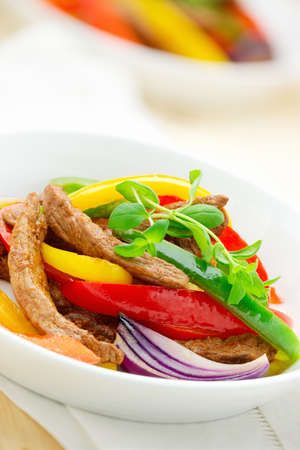 Stir-fried beef with tomato sauce, paprika and red onion