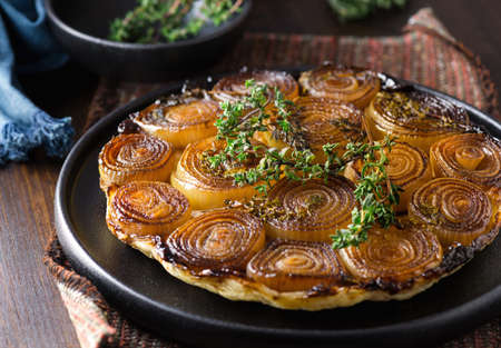 French traditional rustic onion Tarte tatin with balsamic vinegar, caramel and Provence herbs Stockfoto