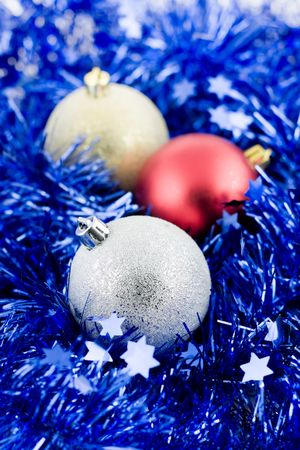 christmas colored balls in an environment of  a blue tinsel vertical frame more soft focus photo