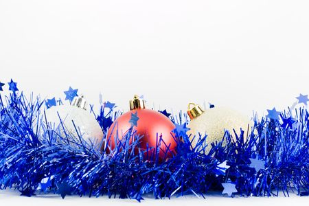 christmas colored balls in an environment of  a tinsel on a white background photo
