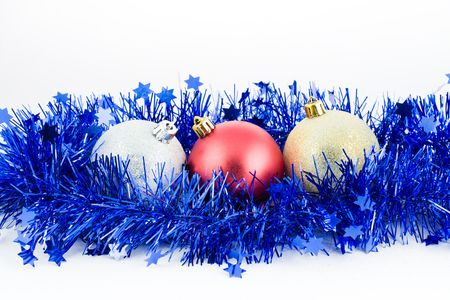 christmas colored balls in an environment of  a tinsel on a white background top horizontal orientation photo