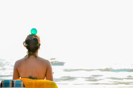 Practicing balance and awareness is good for the health and spiritual growth. Here a woman is practicing the same while relaxing at beach of the Goa.