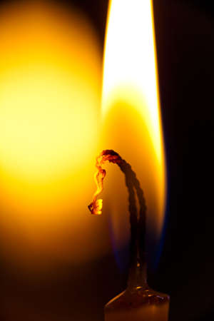 Flame burning candles photographed close-ups so that visible charring of the wick photo