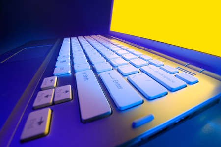 close range: Modern laptop photographed at close range wide-angle lens with the effect of colored light Stock Photo