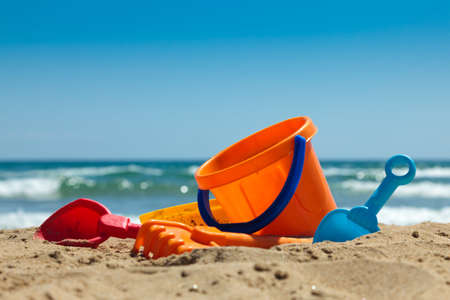 arena: Juguetes de playa de los niños - baldes, pala y pala sobre la arena en un día soleado