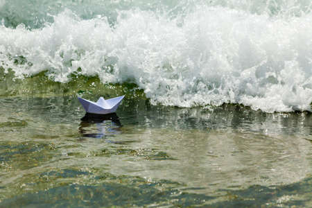 Paper boat and sea foam wave photo
