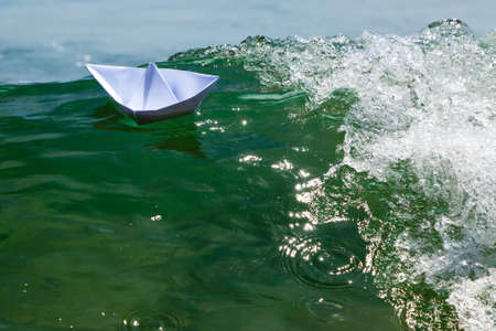 Paper boats on top of the foam of a sea wave photo
