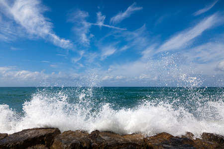 spume: The waves breaking on a stony beach, forming a spray