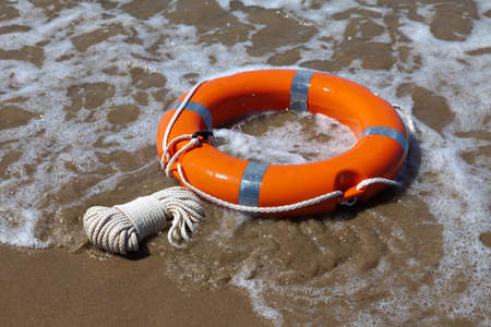 Red lifebuoy lies on the sand on the beach in foamy waves photo