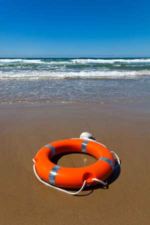 flotation: Red lifebuoy lying on the sand on the beach Stock Photo