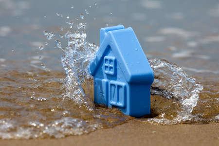 파도에 덮여 모래에 파란 플라스틱 장난감 집, 스프레이를 형성 - 갑작스런 홍수에 대한 은유